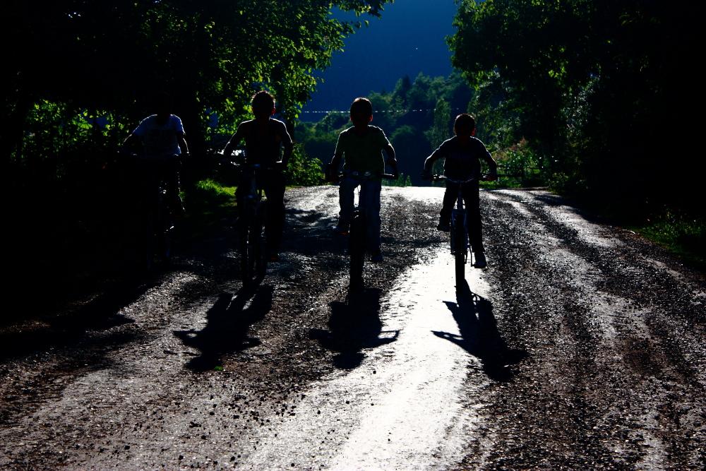 Bisikletli çocuklar ve gün akşama dönerken uzayan gölgeleri