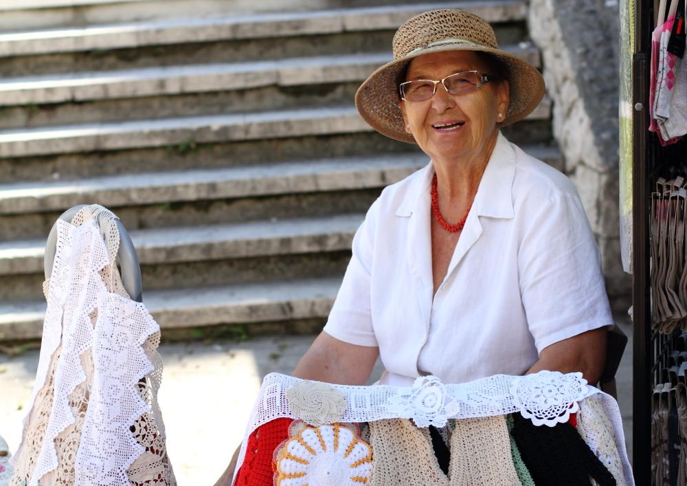 Rita teyze, pazar yerindeki tezgahında el emeği göz nuru tığ işlerini hem üretiyor hem de satıyor
