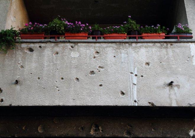 Mostar'da buz gibi kurşun izleri arasından yeşeren, hayata tutunan rengarenk çiçeklerin sıcaklığı karşılar
